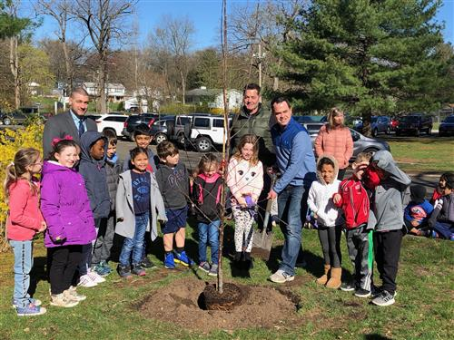 Principal, students and Senator Carlucci standing around the tree they planted.